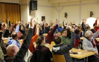 Die versammelten Mitglieder geben per Handzeichen ihre Zustimmung zum Weiterbau (Foto: Alexander Link).