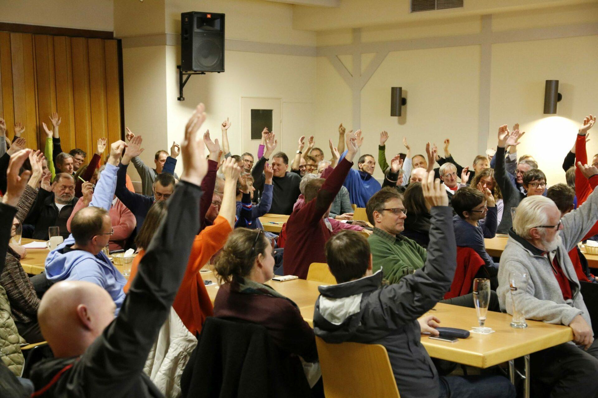 Mitglieder geben per Handzeichen ihre Zustimmung zum Weiterbau