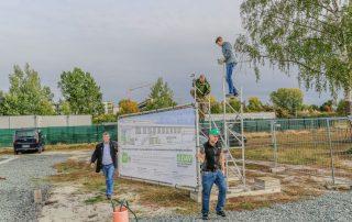 Die Bautafel wird zur Baustelle getragen (Foto: L. Kügel).