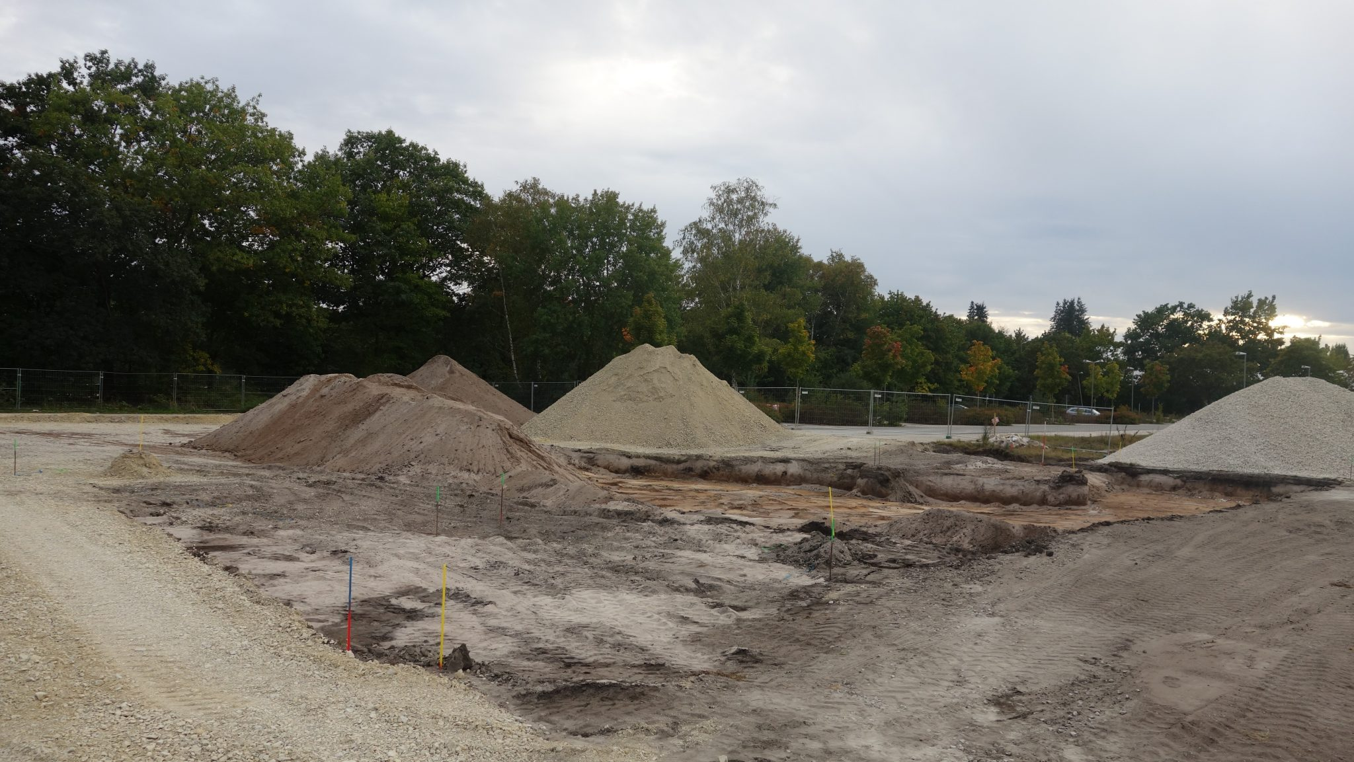 """Blick von """"hinten"""" auf den mit Erd- und Kieshäufen beladenen Parkplatz des Röthelheimbads (Foto: A. Knisch)"""
