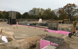 Blick auf die Baustelle mit gut sichtbarer Verschalung des Aufzugs, der Bodenplatte und der rosanen Dämmung (Foto: A. Knisch)